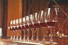 Fileira dos vidros com vinho tinto Foto de Stock