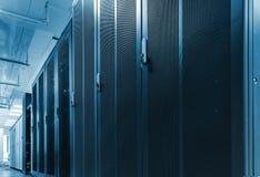 Fileira longa das cremalheiras com as portas da malha no centro de dados grande A caixa do hardware do servidor com comunicações  fotos de stock royalty free