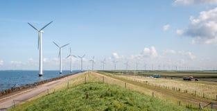 Fileira longa dos moinhos de vento ao lado da estrada, com muito tráfego Fotografia de Stock