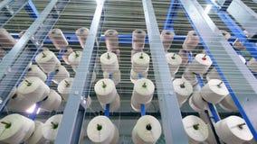Fileiras das bobinas, enroladas com fibra em uma planta de matéria têxtil filme