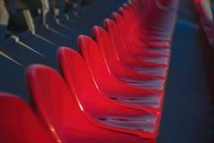Fileiras das cadeiras plásticas brilhantes vazias, assentos da tribuna no estádio, fundo diagonal, foco seletivo Imagem de Stock