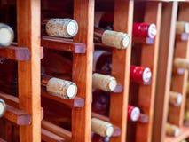 Fileiras das garrafas de vinhos vermelhos e brancos na cremalheira de madeira do vinho imagem de stock