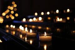 Fileiras das velas em uma igreja fotos de stock
