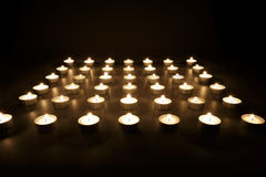 Fileiras das velas votivas que queimam-se na escuridão Fotos de Stock