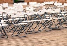 Fileiras de cadeiras modernas brancas vazias no assoalho de madeira do teatro fotos de stock