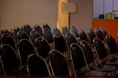 Fileiras de cadeiras pretas com fundo do quadro de avisos imagem de stock