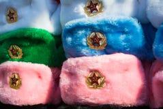 Fileiras de chapéus do inverno do russo de cores diferentes com os emblemas do exército no mercado de rua na rua velha de Arbat Foto de Stock Royalty Free