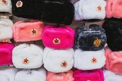 Fileiras de chapéus do inverno do russo de cores diferentes com os emblemas do exército na lembrança popular icónica do mercado d Fotografia de Stock Royalty Free