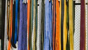 Fileiras de correias coloridas na loja para homens e mulheres foto de stock