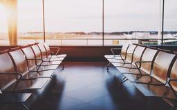 Fileiras de Empyy dos assentos na sala de espera do aeroporto foto de stock