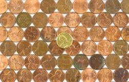 Fileiras de moedas de um centavo usadas com a moeda de um centavo do ouro no meio Fotografia de Stock