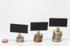 Fileiras de moedas do baht tailandês e da placa preta pequena para o conceito da finança e da operação bancária com fundo branco  Fotos de Stock Royalty Free