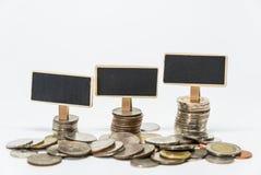 Fileiras de moedas do baht tailandês e da placa preta pequena para o conceito da finança e da operação bancária com fundo branco  Fotos de Stock