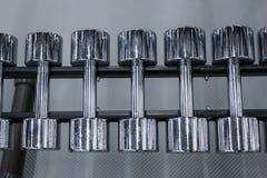 Fileiras de pesos do metal na cremalheira no gym ou no clube de esporte Equipamento de treino do peso Fotografia de Stock Royalty Free