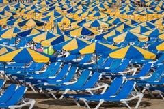 Fileiras de sunbeds azuis com os parasóis azuis e amarelos na praia Playa de Porto Rico nas Ilhas Canárias fotos de stock
