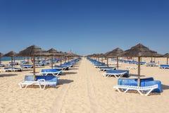 Fileiras de vadios e de guarda-chuvas do sol para tomar sol aos turistas Tavira, Portugal, o Algarve Imagens de Stock