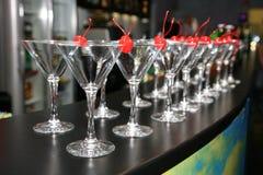 Fileiras delgadas de vidros de cocktail vazios na barra Cereja vermelha decorativa Imagens de Stock Royalty Free