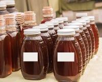 Fileiras dos frascos com mel ambarado fotografia de stock royalty free