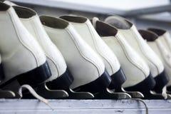 Fileiras dos patins de gelo brancos, material desportivo do inverno, prateleiras com patins imagem de stock