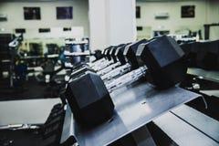 Fileiras dos pesos no gym com tom cinzento Fotografia de Stock