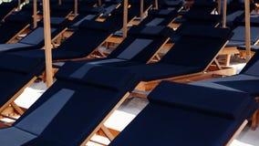 Fileiras dos sunbeds sob guarda-chuvas de praia no recurso tropical Fotos de Stock Royalty Free