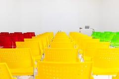 Fileiras prontos para uso de cadeiras coloridas na sala de conferências com pro foto de stock royalty free