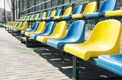 Fileiras vazias de assentos azuis e amarelos na corte do esporte da escola, exteriores fotos de stock