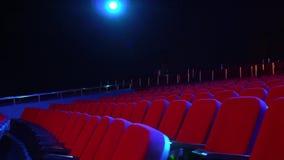 Fileiras vazias dos assentos no salão do cinema Cinema vazio com assentos vermelhos na sala escurecida com luz do projetor sobre vídeos de arquivo