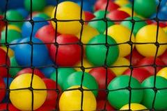 Filet avec de diverses boules en plastique colorées pour le jeu des enfants Photographie stock libre de droits