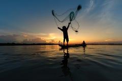 Filet de lancement de pêcheur sur la pêche de bateau au lac Photos stock