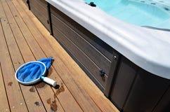 Filet de nettoyage de piscine sur le decking en bois photo libre de droits