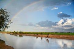 Filet de pêche de bâti de garçon en rivière avec l'arc-en-ciel ci-dessus et gisements de riz derrière lui Images stock