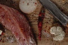 Filet de porc cru frais sur la planche à découper en bois à l'oignon, à l'ail et au couteau photographie stock