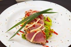 Filet de thon sur le plat blanc avec de la salade et la sauce de soja Photographie stock libre de droits