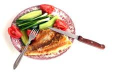Filet des poissons frits d'un plat avec des concombres, des tomates, des oignons et la fourchette Image stock