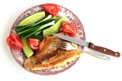 Filet des poissons frits d'un plat avec des concombres, des tomates, des oignons et la fourchette Photo stock