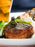 Filet Mignon. Grilled steak wrapped in bacon, with grilled vegetables, mashed potatoes, garlic toast, and lemon iced tea royalty free stock photo