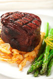 Filet Mignon. Thick Filet mignon served with crispy onions and asparagus Royalty Free Stock Image