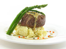Filet mignon 2. Filet mignon over mashed potatoes with asparagus on a white plate isolated on white Royalty Free Stock Images