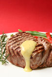Filet Mignon. Thick filet mignon with bearnaise sauce, green beans and red peppers, and a sprig of rosemary.  Red background Stock Images