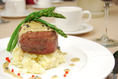 Filet mignon. Over mashed potatoes with asparagus on a restaurant table Stock Photography