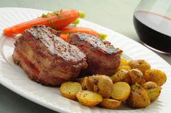 Filet Mignon. Bacon wrapped filet mignon served with potatoes and carrots Royalty Free Stock Photography