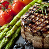 Filet Mignon with Asparagus and Cherry Tomatoes. Filet mignon grilled beef steak, with asparagus and cherry tomatoes.  Isolated on white Royalty Free Stock Image