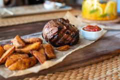 Filet Mignon with fried potatoes and tomato sauce on a wooden Board with Cutlery stock photo