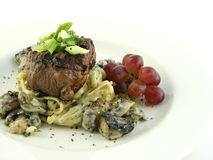 Filet mignon over pasta Stock Images