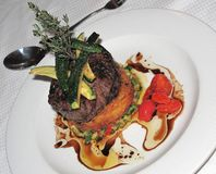 Filet Mignon on Potato Rosti. Filet Mignon beef steak on bed of potatoes and vegetables with zucchini slices on top stock photos