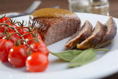Filet mignon. Sliced filet mignon with baked tomatoes and sage royalty free stock photo