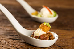 Filet mignon with spices, lemon zest, creamy curd and fried banana in a spoon Royalty Free Stock Photos
