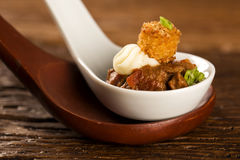 Filet mignon with spices, lemon zest, creamy curd and fried banana in a spoon Stock Images