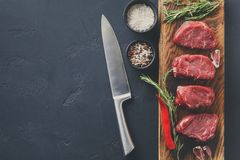 Filet mignon steaks and spices on wood at black background. Raw filet mignon steaks with herbs and spices. Ingredients for restaurant dish. Fresh meat, salt Royalty Free Stock Images